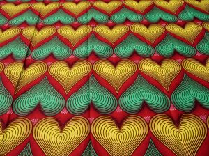 Red and green heart shaped african wax print fabric background image